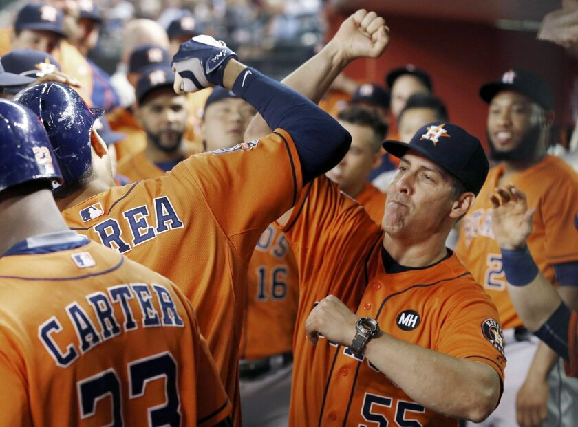 The Astros' Carlos Correa, second from left, celebrates his home run against the Arizona Diamondbacks with assistant hitting coach Alan Zinter, right, during the fourth inning of a baseball game Friday, Oct. 2, 2015, in Phoenix.