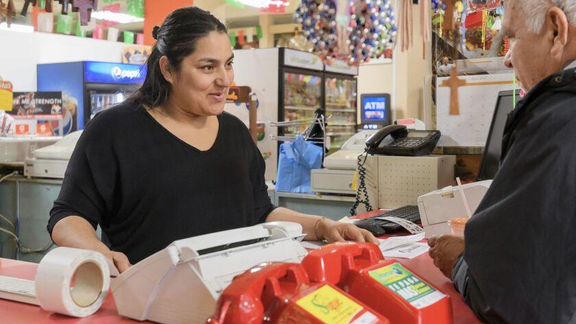 Maria Garcia helps a customer at La Azteca Market in Grand Island.