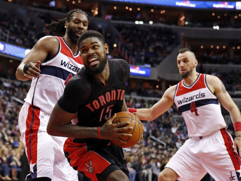 Toronto forward Amir Johnson spins away from Washington forward Nene, left, and center Marcin Gortat during the first half of the Raptors' 120-116 overtime victory Saturday over the Wizards.