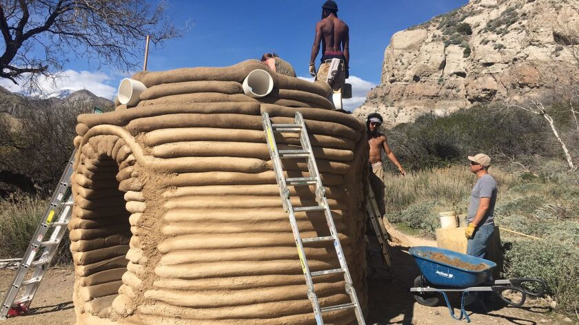 "Earth-bag construction specialists work on Sherin Guirguis' ""One I Call."""