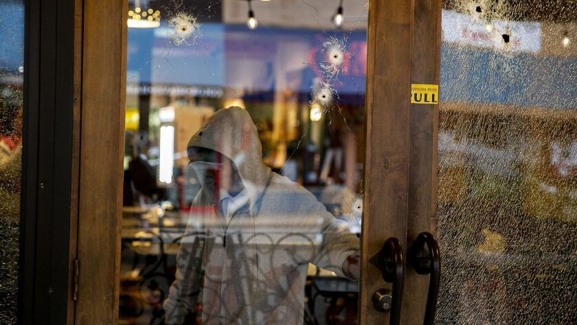 "Bullet holes pierced the glass of The Asian Bistro restaurant in Hillcrest after a suspect released a ""hail of gunfire"" into the restaurant. On Wednesday, people surveyed the damage inside the store."