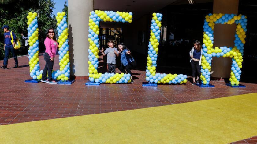 Janet Mejía, izquierda, de Sun Valley y sus hijos Emmanuel, Jennifer y Samantha, de izquierda a derecha, posan para la fotografía junto a globos que forman las siglas de UCLA, durante el día anual de los Bruins.