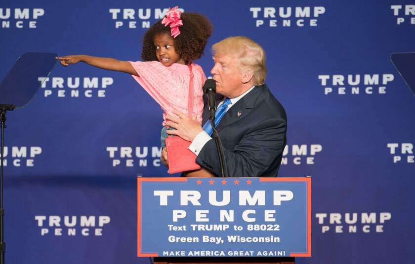 Donald Trump holds a child during a campaign rally in Green Bay, Wis., on Oct. 17.