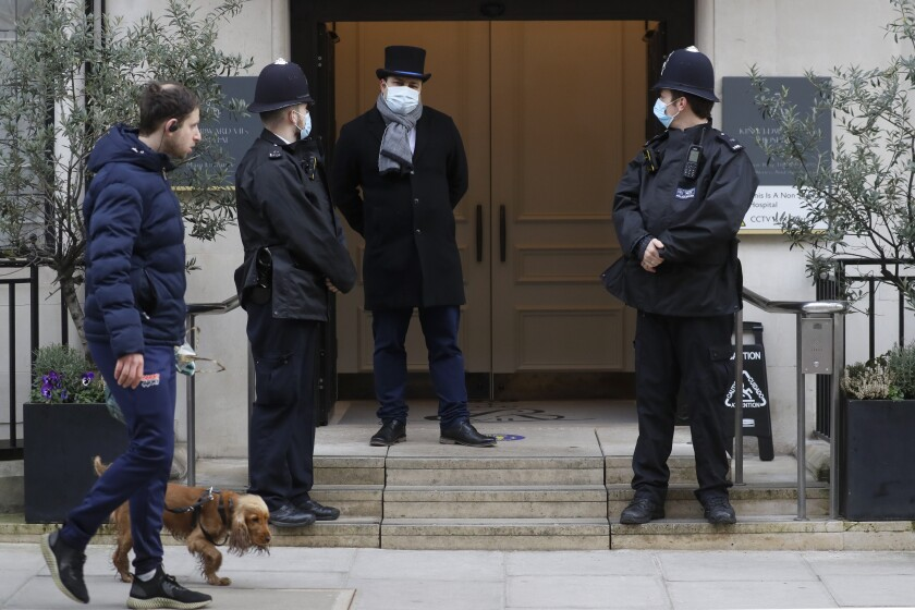 "A man walks by with a dog as police officers stand outside King Edward VII's hospital in London, Tuesday, Feb. 23, 2021. Britain's Prince Philip was admitted to the private King Edward VII's Hospital in London on Tuesday, Feb. 16, after falling ill. Buckingham Palace said the husband of Queen Elizabeth II was expected to remain in the hospital into this week for a period of ""observation and rest."" (AP Photo/Kirsty Wigglesworth)"