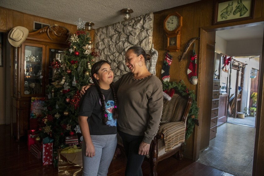 A mother and daughter stand in front of a Christmas tree and stockings in their home