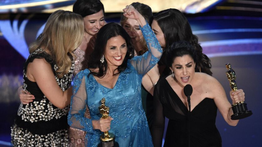 """Melissa Berton and Rayka Zehtabchi accept the award for best documentary short subject for """"Period. End of Sentence"""" at the Oscars in Los Angeles on Sunday."""