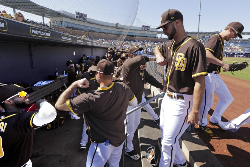 Padres players practice good hygiene as they bump elbows rather than slap hands while heading into the dugout between innings of Wednesday's game against the Royals.