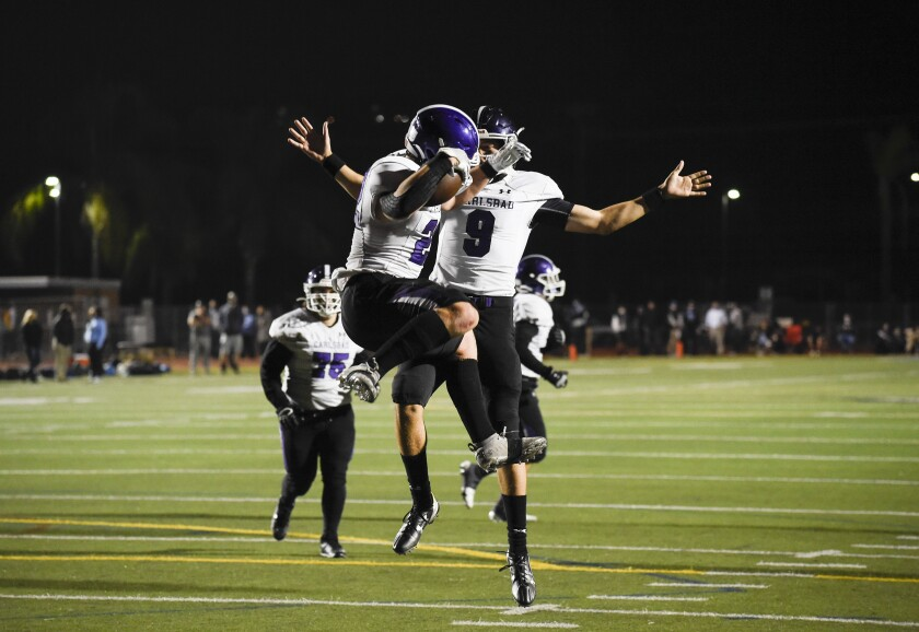 Carlsbad's Anthony Ferrelli (left) celebrates with quarterback Aidan Sayin (9) after scoring on a two-point conversion.