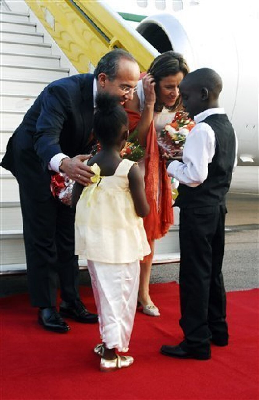 Mexico's President Felipe Calderon and his wife Margarita Zavala receive flowers from Ugandan children upon arriving at Entebbe International Airport for the upcoming African summit, Saturday, July 24, 2010, in Kampala, Uganda.  African heads of state are due to meet in the Ugandan capital, Kampala