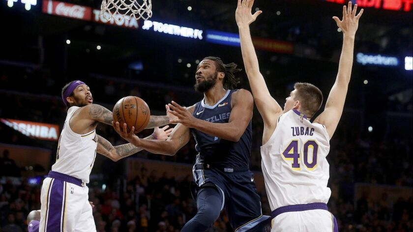 Memphis Grizzlies guard Wayne Selden (7) drives to the basked guarded by Lakers forward Brandon Ingram (14) and center Ivica Zubac (40) at the Staples Center on Sunday.