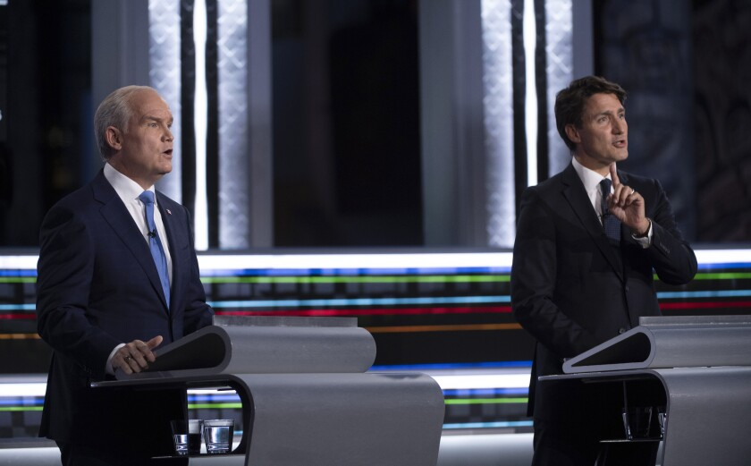 FILE - Conservative leader Erin O'Toole, left, and Liberal leader Justin Trudeau speak during the federal election French-language leaders debate, Wednesday, Sept. 8, 2021, in Gatineau, Que. Trudeau called the early election for Monday, Sept. 20 in hopes of winning a majority of seats in Parliament, but has faced criticism for calling a vote during a pandemic in order to cement his hold on power. (Justin Tang/The Canadian Press via AP)