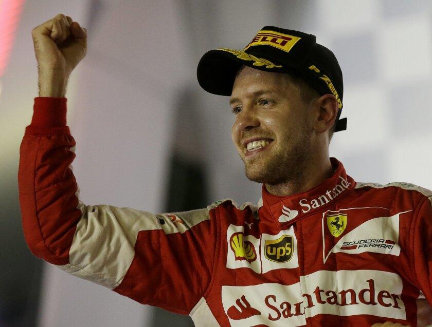 Ferrari driver Sebastian Vettel of Germany celebrates on the podium after winning the Singapore Formula One Grand Prix on the Marina Bay City Circuit in Singapore, Sunday, Sept. 20, 2015.(AP Photo/Mark Baker)