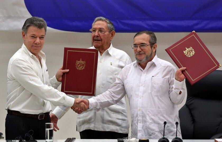"""El delegado de las FARC en Cuba, Rodrigo Londoño Echeverri, alias """"Timochenko"""" (d) y el presidente de Colombia, Juan Manuel Santos (i) junto a el presidente de Cuba, Raúl Castro (c) sostienen en sus manos el acuerdo de paz entre el Gobierno colombiano y las FARC, durante la ceremonia en La Habana (Cuba) hoy, jueves 23 de junio de 2016, del acuerdo para el cese al fuego en Colombia. El acto para oficializar el acuerdo de cese al fuego bilateral y definitivo en Colombia comenzó hoy en La Habana, encabezado por el presidente Juan Manuel Santos y por Timochenko, máximo líder de las FARC, y con la asistencia de seis presidentes de la región y el secretario general de la ONU. EFE/ALEJANDRO ERNESTO"""