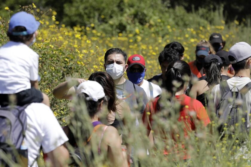 Visitors share a narrow hiking path at Eaton Canyon Natural Area Park on Sunday in Pasadena.