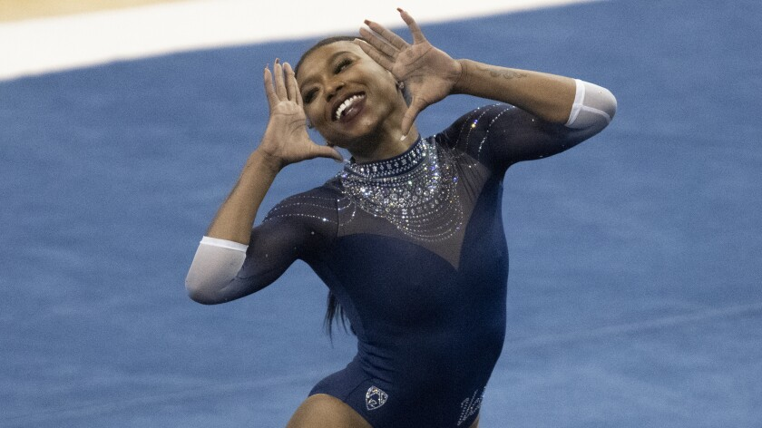 UCLA's Nia Dennis holds her hands up on either side of her face during a floor routine.