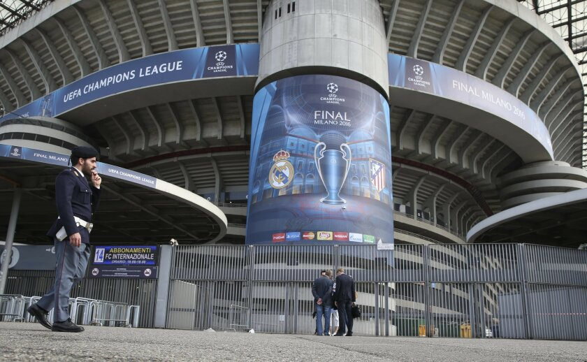 A police officer patrols outside the San Siro stadium, in Milan, Italy, Wednesday, May 25, 2016. The Champions League soccer final between Real Madrid and Atletico Madrid will be held at the San Siro stadium on Saturday, May 28, 2016. (AP Photo/Luca Bruno)