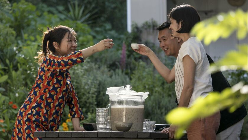 Yong Ha Jeong, left, a Los Angeles-based sool brewer, cheers with friends with a cap of makgeolli.