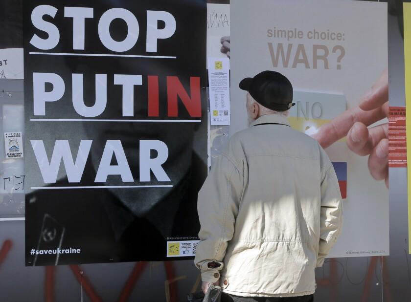 A man looks at anti-Putin posters in Kiev, Ukraine.