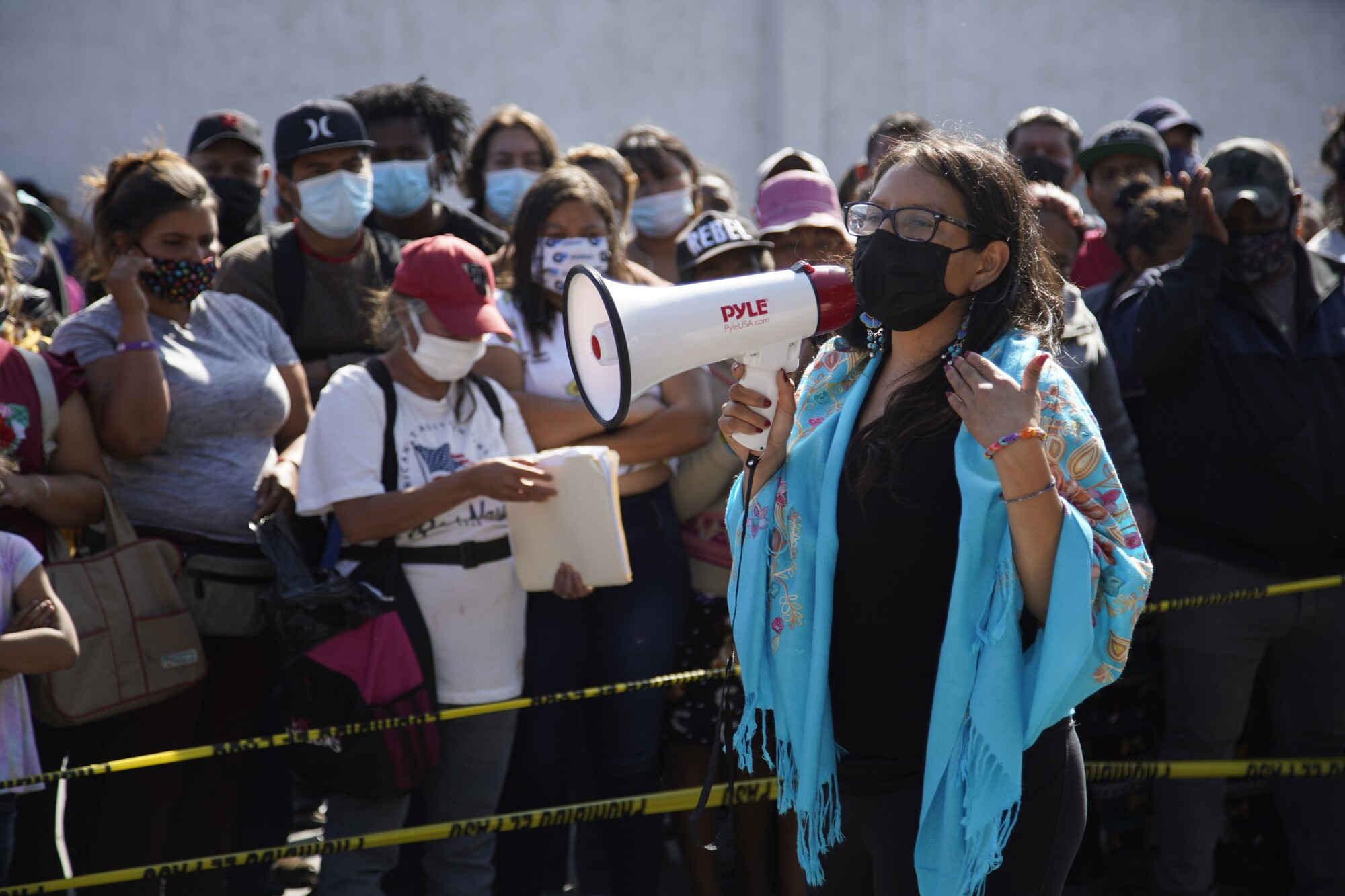 A woman with a megaphone speaks to a group of people.