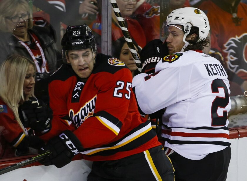 Chicago Blackhawks' Duncan Keith, right, checks Calgary Flames' Freddie Hamilton during first period NHL hockey action in Calgary, Saturday, March 26, 2016. (Jeff McIntosh/The Canadian Press via AP)