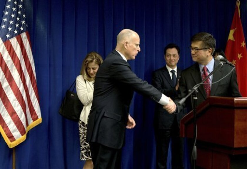 U.S. Ambassador to China Gary Locke, right, shakes hand with California Gov. Jerry Brown, as Chinese Vice Minister of Commerce Wang Chao, center, look on during a Trade and Investment reception at the U.S. Embassy in Beijing Wednesday, April 10, 2013. (AP Photo/Andy Wong, Pool)