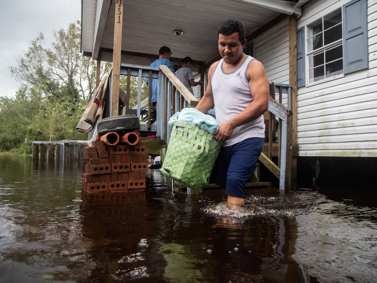 Chavez Gallegos helps his family move out of a flooded home in Kinston, N.C., in the aftermath of Hurricane Florence.