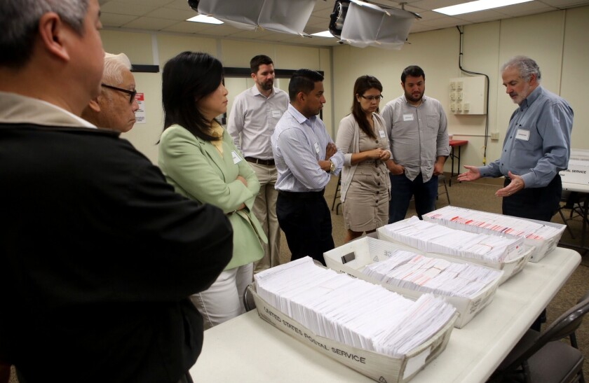 O.C. election officials and observers prepare to review ballot materials.