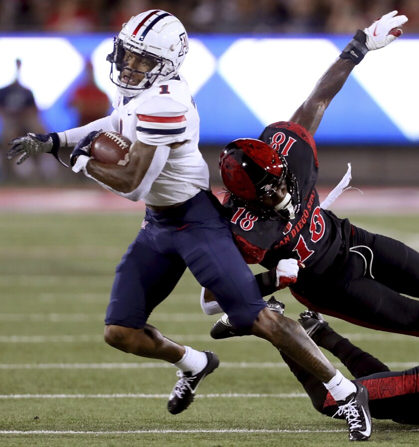 Arizona receiver Stanley Berryhill III bounces off San Diego State safety Trenton Thompson (18) after his catch and heads for the end zone for a touchdown during the first half of an NCAA college football game Saturday, Sept. 11, 2021, in Tucson, Ariz. (Kelly Presnell/Arizona Daily Star via AP)