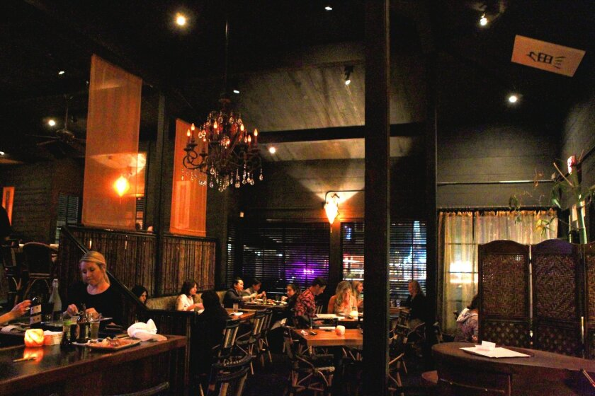 Zenbu Sushi evokes a lounge atmosphere with dim lighting, candles on wooden tables, bamboo accents, Asian-inspired decor, and world-beat music playing in the background. Photo by Daniel K. Lew