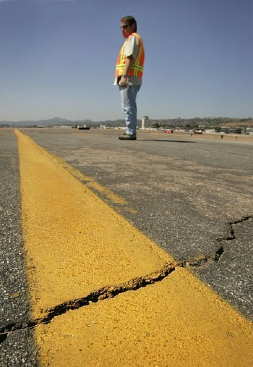 Roger Griffiths, manager of Gillespie Field in El Cajon, inspected cracks in one of the facility's two taxiways that will be repaired using federal stimulus funds. (Howard Lipin / Union-Tribune)