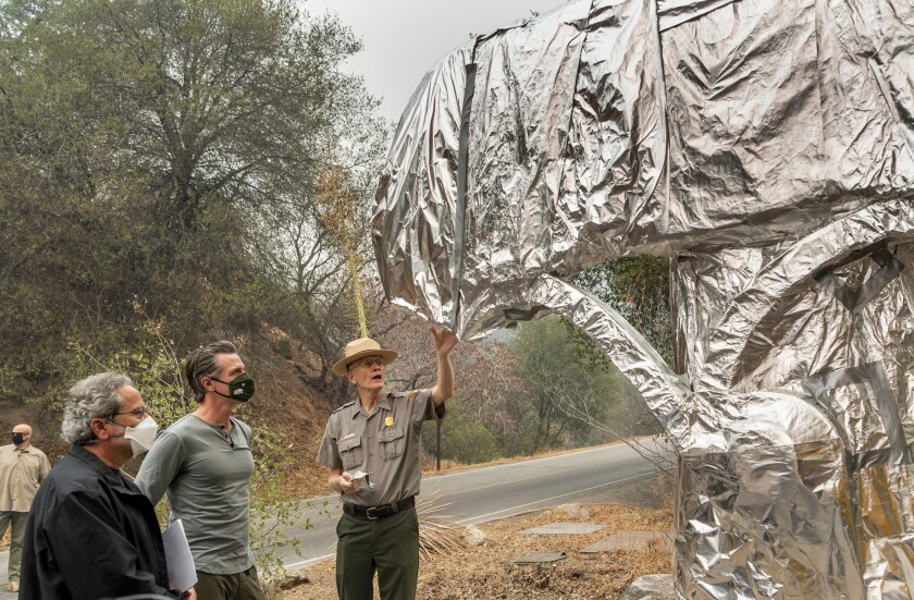 State Assembly Member Richard Bloom, D-Santa Monica, left, and California Gov. Gavin Newsom, second left, listen to Superintendent of Sequoia and Kings Canyon National Parks Clay Jordan, right, talk about the protective structure wrap used to protect the welcome sign and giant sequoia trees from the KNP Complex Fire, on Thursday, Sept. 23, 2021, in Sequoia National Park, Calif. Newsom on Thursday approved nearly $1 billion in new spending to prevent wildfires, signaling a policy shift in a state that historically focused more on putting out fires than stopping them before they start. (Ron Holman/The Times-Delta via AP)