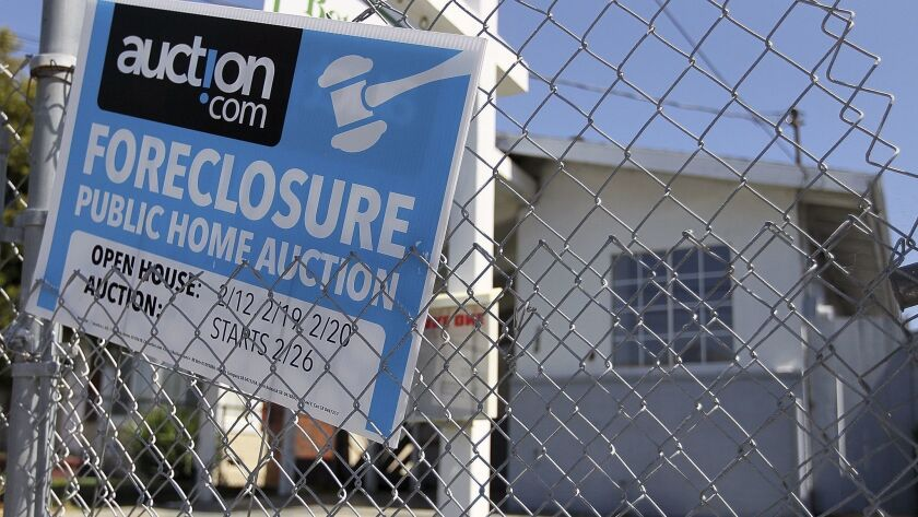 A foreclosure sign hangs on a fence in front of a foreclosed home in Richmond, Calif.