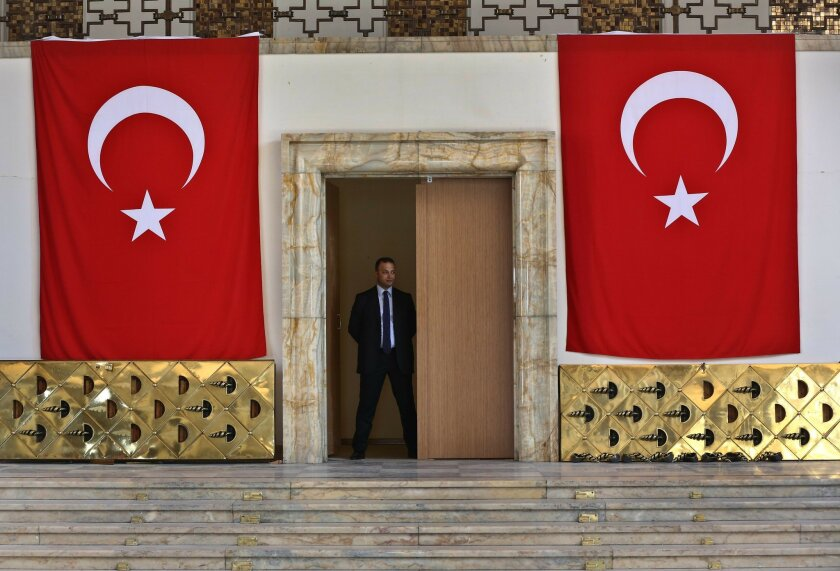 A Turkish parliament security man stands guard next to the broken yellow copper doors laid on the ground at the entrance of the assembly hall at the parliament building which was attacked by the Turkish warplanes during the failed military coup last Friday, in Ankara, Turkey, Tuesday, July 19, 2016