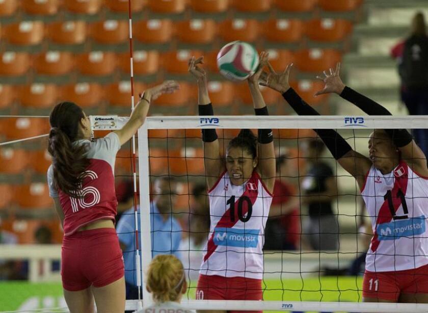 La mexicana Melanie Parra (i) ataca el balón ante la peruanas Zoila La Rosa (C), y Clarivett Yilescas durante un partido entre México y Perú por la XVII Copa Panamericana de Voleibol, en Santo Domingo (República Dominicana). EFE