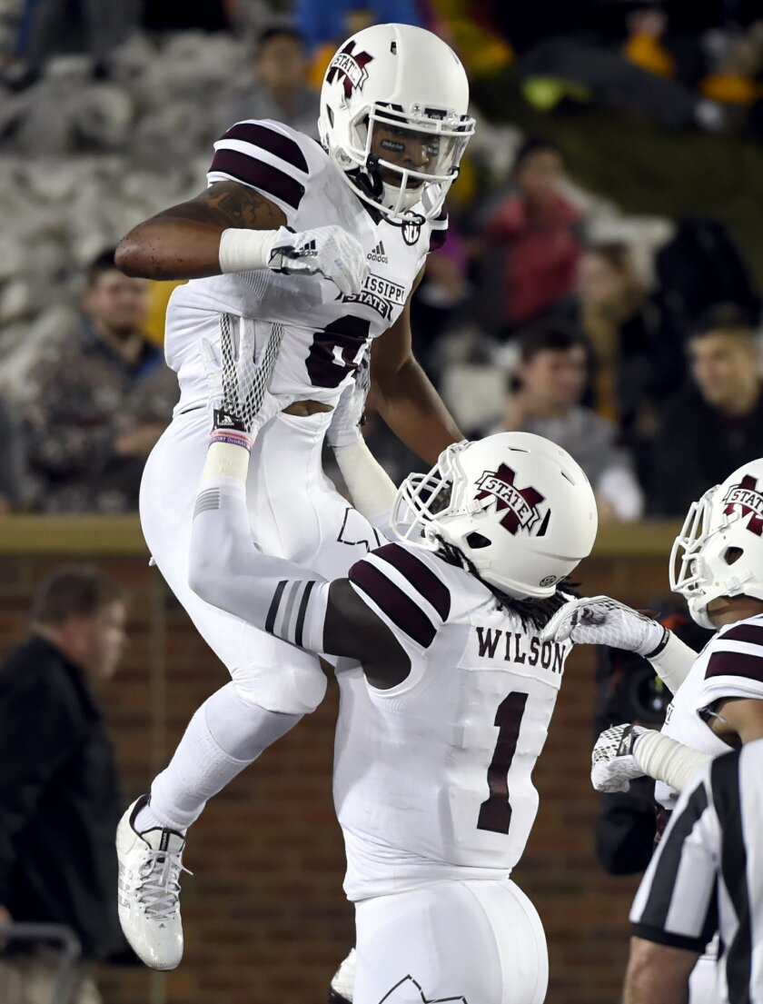 Mississippi State wide receiver Fred Ross, top, is congratulated by De'Runnya Wilson after catching a 36-yard touchdown pass during the first half of an NCAA college football game against Missouri on Thursday, Nov. 5, 2015, in Columbia, Mo. (AP Photo/L.G Patterson)