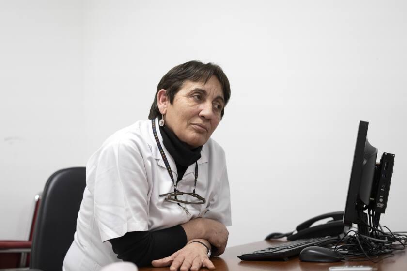 """La Dra. Julia Galzerano se sienta para una entrevista en el hospital donde trabaja en Montevideo, Uruguay, el viernes 17 de septiembre de 2021. Galzerano tiene un cartel en su oficina que da la bienvenida a su consulta de """"Policlínica medicina canábica"""". (AP Foto/Matilde Campodónico)"""