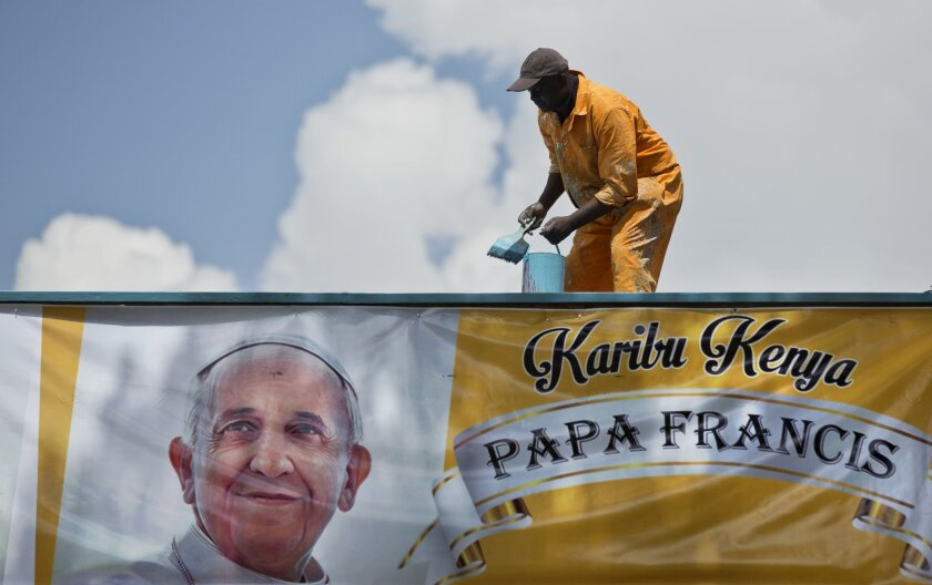 "A workman finishes painting a roof at the site where the Papal Mass will take place, above a banner in Swahili reading ""Welcome to Kenya"", in Nairobi, Kenya Tuesday, Nov. 24, 2015. The Kenyan government has declared a national public holiday Thursday on the day that Pope Francis is due to celebrate mass on the grounds of the University of Nairobi with large crowds expected to flock to the event. (AP Photo/Ben Curtis)"