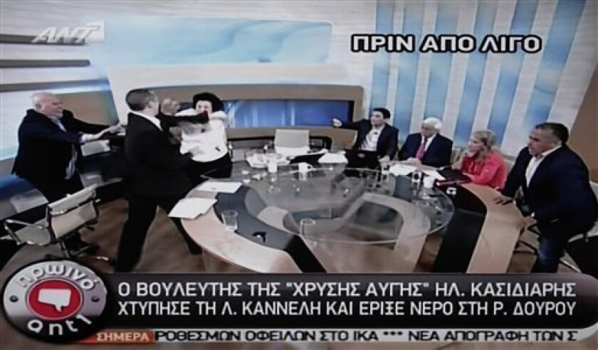 In this image taken off a TV screen, Ilias Kasidiaris, 2nd left, spokesman of Greece's extremist far-right Golden Dawn party, who was elected to Parliament in the country's recent inconclusive polls, physically assaults Liana Kanelli, a female member of the Parliament for the Greek Communist party,
