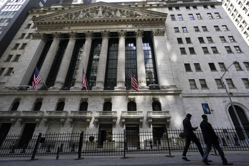 Two people walk past the New York Stock Exchange.