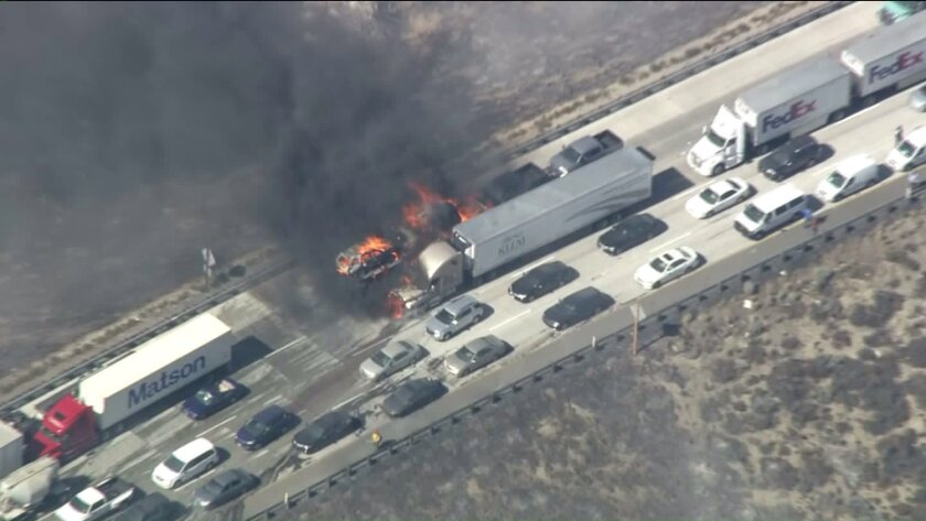A big-rig burns on the 15 Freeway in the Cajon Pass as a brush fire that has grown to more than 2,000 acres moves toward two mountain communities.