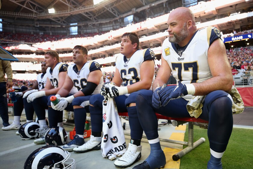 Rams offensive tackle Andrew Whitworth, right, sits during a game against the Cardinals on Dec. 1, 2019.