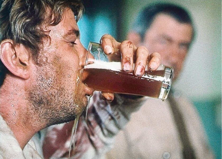 """Gary Bond is on his way to a drunken stupor in a scene from the 1971 movie """"Wake in Fright."""""""