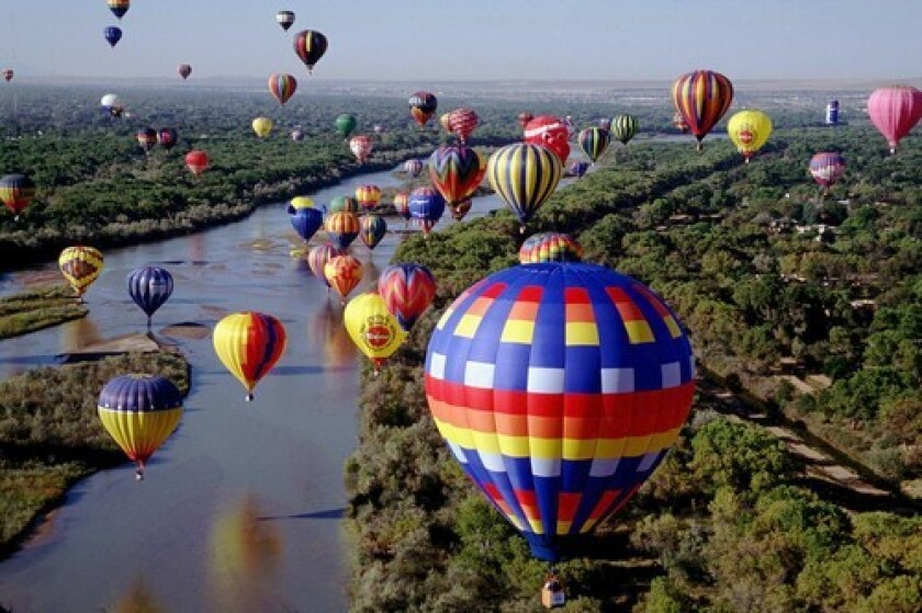 Colorful hot-air balloons float gracefully over the Rio Grande during the New Mexico city's annual festival. At top, turquoise finds draw canny shoppers to Albuquerque.