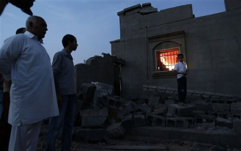 In this photo taken on a government organized tour, local residents stand next to a damaged house in Tripoli, Libya, on Sunday, June 5, 2011. Libyan officials claim that during a NATO airstrike, a rocket targeted a nearby military site hit a residential area and damaged several houses. (AP Photo/Ivan Sekretarev)