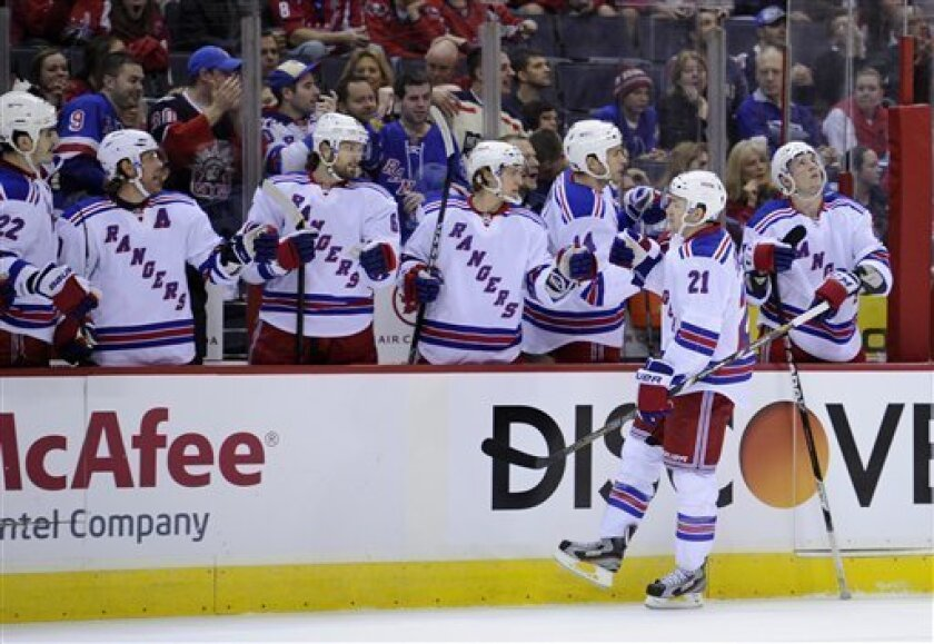 New York Rangers center Derek Stepan (21) celebrates his goal with the bench against the Washington Capitals during the first period of an NHL hockey game, Sunday, March 10, 2013, in Washington. (AP Photo/Nick Wass)