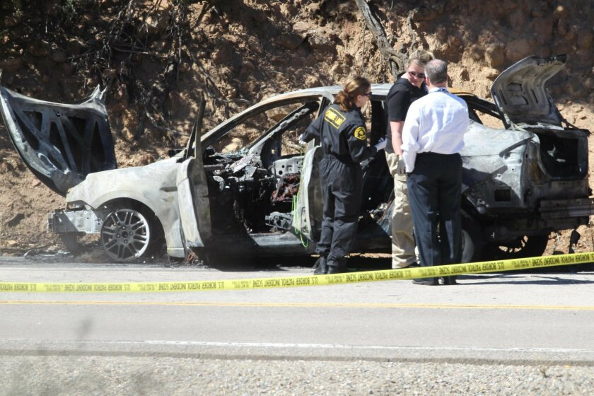 Sheriff investigators pored over the burnt remains of a car that burst into flames on Old Highway 80 near Sunrise Highway on March 15 after it was disabled by spike strips deployed by Border Patrol agents during a pursuit.
