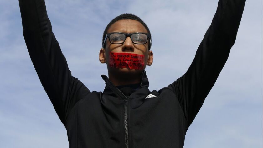 High school sophomore Kobey Lofton holds up a sign during an anti-violence march to protest gun viol