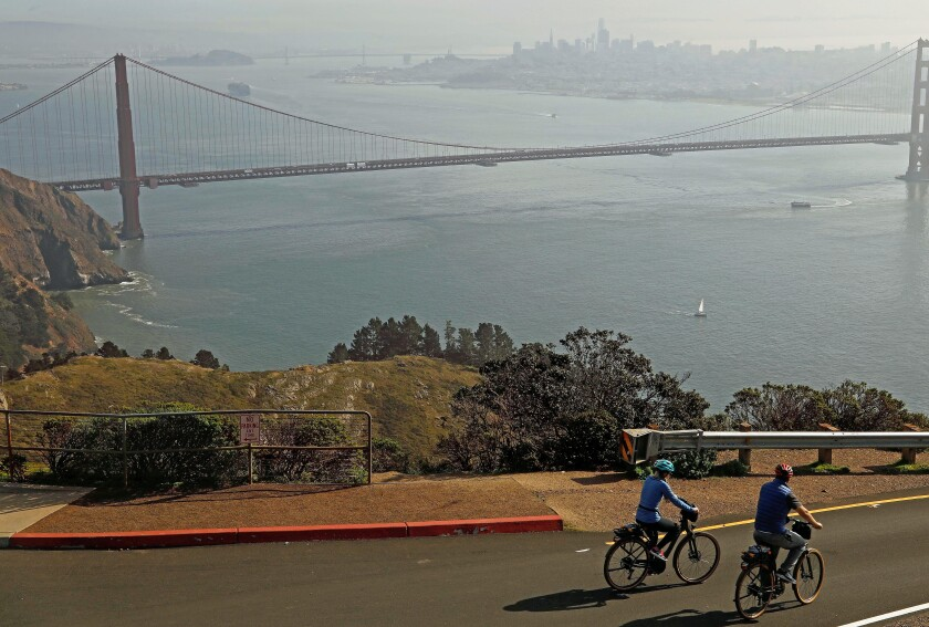 Renata Lima, left, and husband Lucas Lima, from Sao Paulo, Brazil, ride their e-bikes on Hawk Hill in the Marin Headlands.