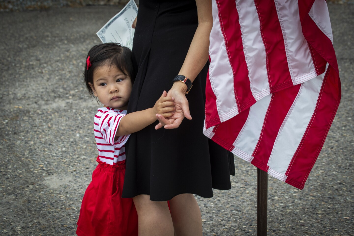 LAGUNA NIGUEL, CA - JUNE 23: Talia Han, 1, hugs her mom, Thao Pham, who's a pop singer with a stage name of Thanh Thao, after taking the oath of allegiance at a drive through citizenship naturalization at the Chet Holifield Federal Building parking lot Tuesday, June 23, 2020 in Laguna Niguel. Pham immigrated to Westminster from Vietnam. About 210-270 people a day have appointments throughout the day for 11 days in seven locations across Southern California. Due to the COVID-19 pandemic, the courts have delegated the authority to U.S. Citizenship and Immigration Services to administer the Oath of Allegiance at the naturalization ceremony. Taking the oath completes the process of becoming a U.S. citizen. (Allen J. Schaben / Los Angeles Times)