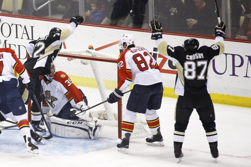 Pittsburgh Penguins' Sidney Crosby (87) celebrates a goal scored by Patric Hornqvist, left, on Florida Panthers goalie Al Montoya (35) in the first period of an NHL hockey game, Sunday, Feb. 22, 2015, in Pittsburgh. (AP Photo/Keith Srakocic)